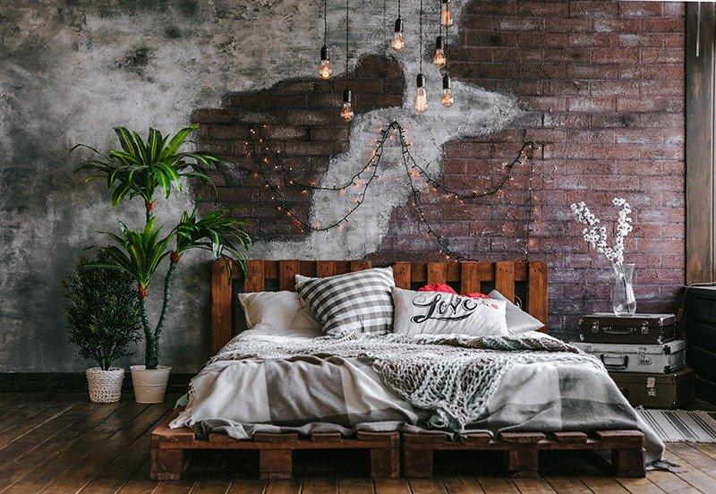 Een bed van pallets staat mooi in een industrieel interieur.